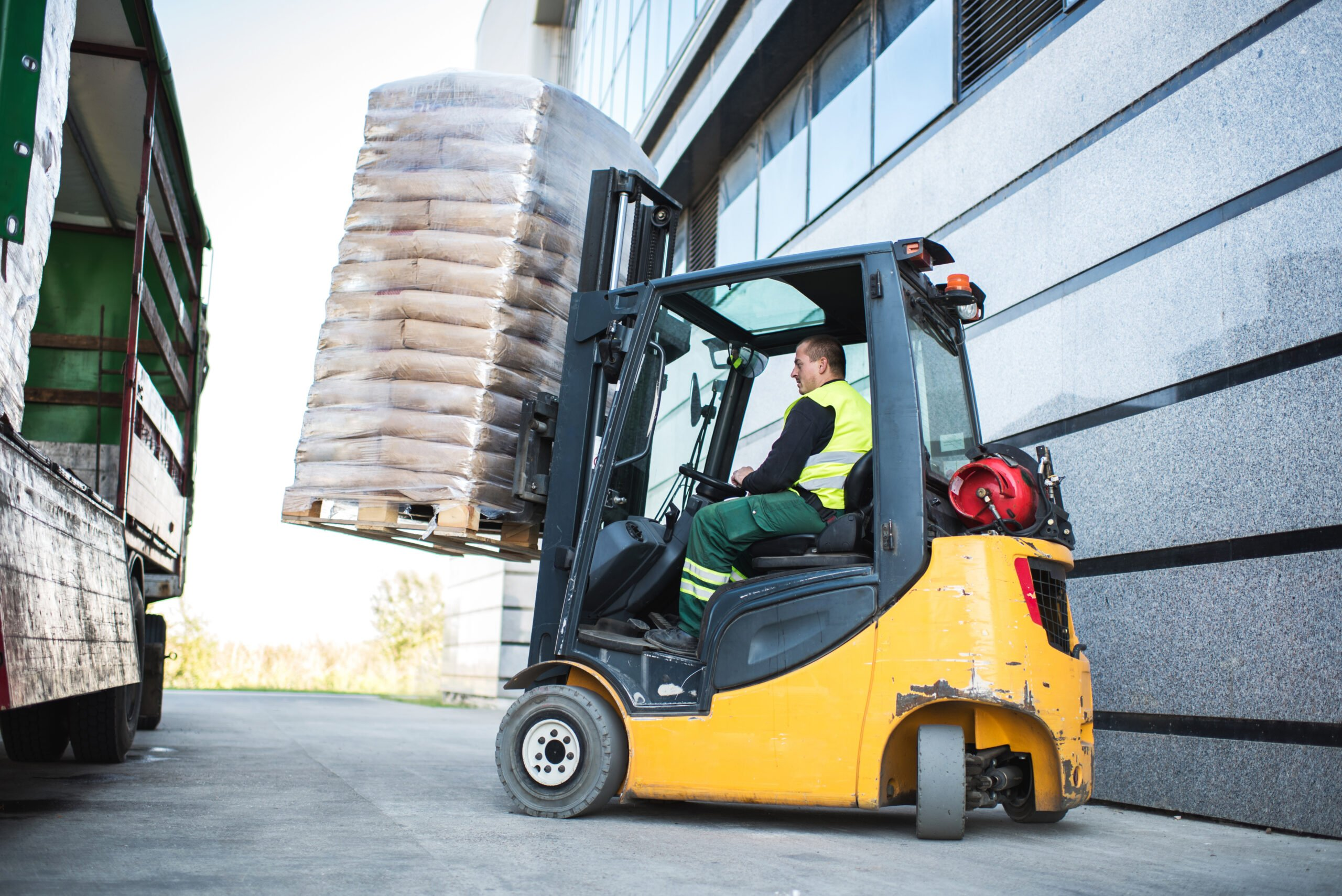 Worker loading pallet with a lpgmforklift into a truck.